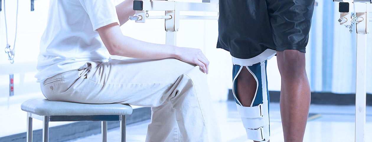 Man receiving care at inpatient clinic after knee injury