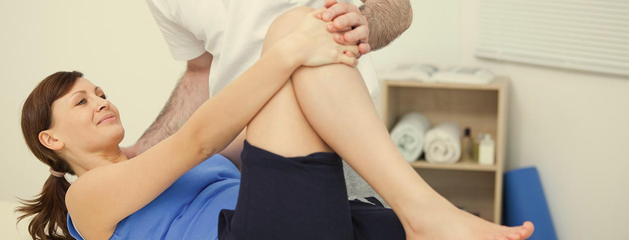 Woman getting helped by physiotherapist, fully insured