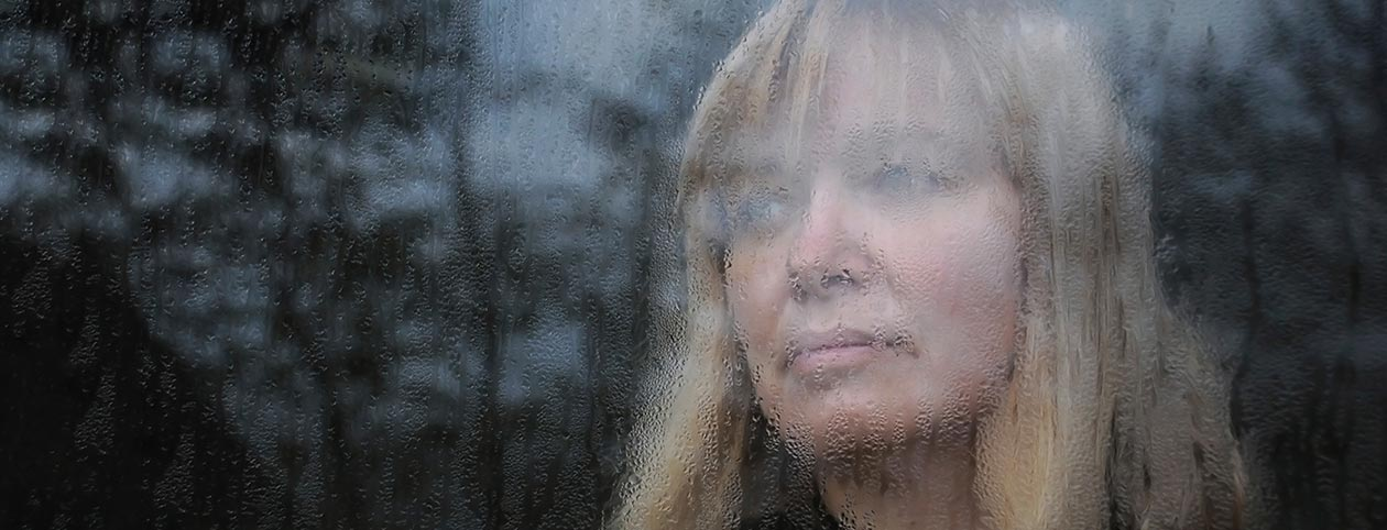 Woman looking out of window with symptoms of depression
