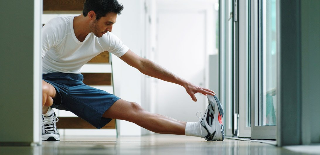 Man doing exercise at home-to minimize cost of physical therapy